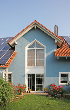 modern new built house and garden, rooftop with solar cells, blue front with lattice window Standard-Bild