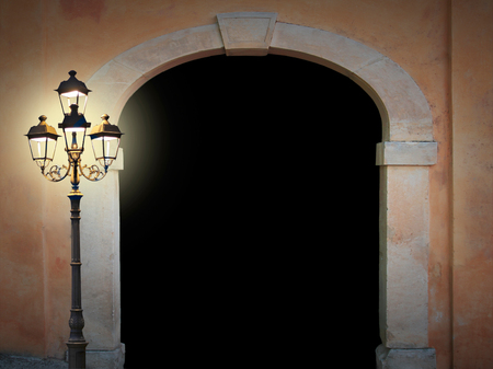 glooming: Vintage arched doorway with glooming lantern on black