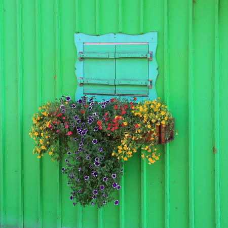 boathouse: Wooden green painted boathouse facade, closed window with flower box
