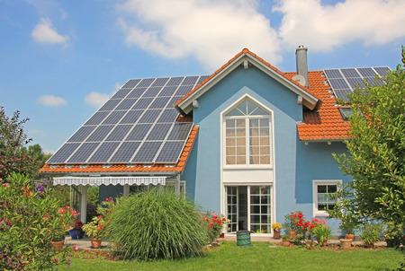 woonwijk: modern nieuw gebouwde huis en tuin, op het dak met zonnecellen, blauw voorzijde met latwerk venster Stockfoto