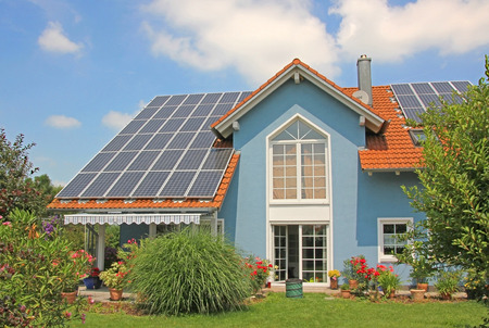modern new built house and garden, rooftop with solar cells, blue front with lattice window