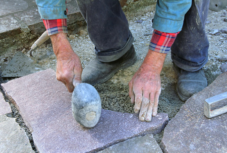 leitender Landschaftsgärtner Einbau eines Steinplatten Fliesen mit einem Gummihammer Lizenzfreie Bilder
