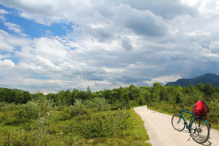 bike riding at isar wetlands, with dramatic cloudy sky, lonely bavarian landscape