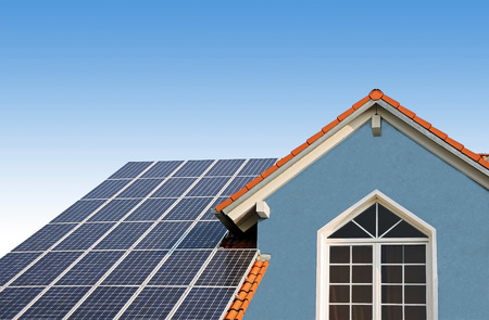 modern new built house, rooftop with solar cells, blue front with lattice window  Stock Photo
