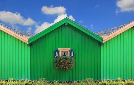 green boat: Front of green boat houses with traditional bavarian window, against blue sky with clouds