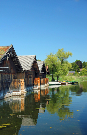 wooden boat houses reflecting in the water of lake staffelsee, bavarian landscape  photo