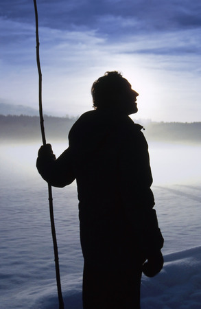 back lighting: Silhouette of sheperd with a crook, wintry morning snow scape