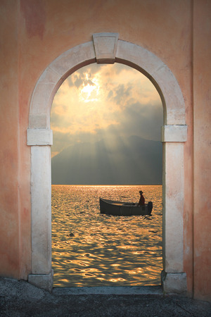 view through door: View through arched door to rowing boat at sunset, romantic mood  Stock Photo