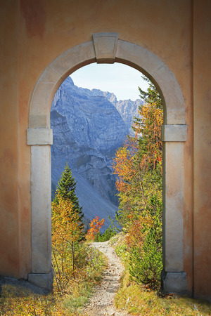 winding hiking trail through arched door, mountainous autumn landscape