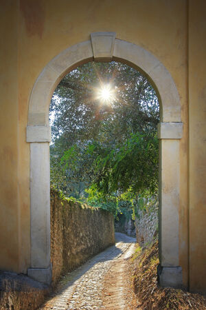 walkway through arched door; ancient footpath with view to olive tree with sunburst  Stock Photo
