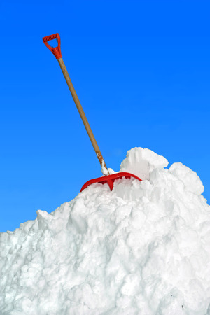 big snow heap and shovel, against blue sky