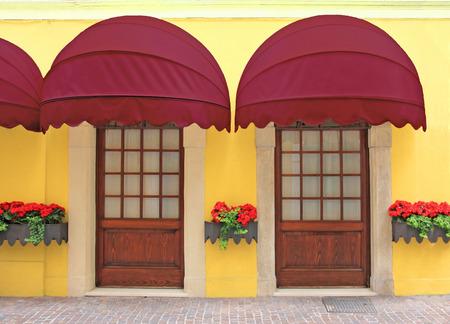 gelbe Fassade mit zwei Eingängen, nostalgischen roten Festzelt, italien