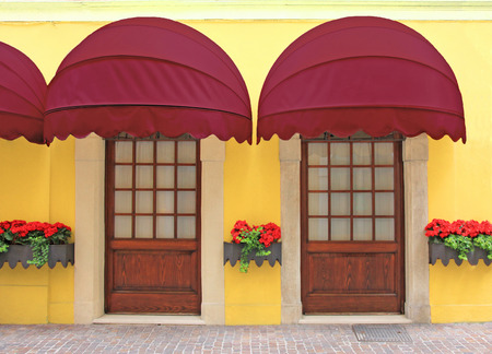 shop front: yellow facade with two entrances, nostalgic red marquee, italy