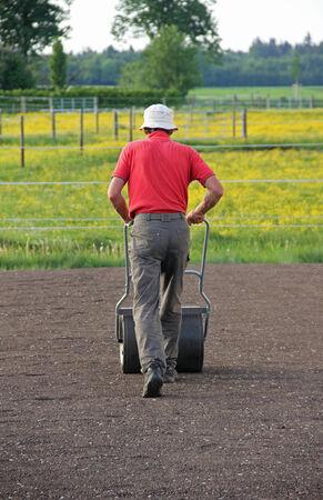 man flattening the soil for preparing garden lawn with a flexible roll