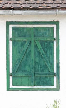 white facade with closed green window shutter