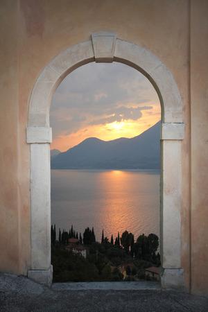 view through door: view through arched door; mediterranean sunset scenery Stock Photo