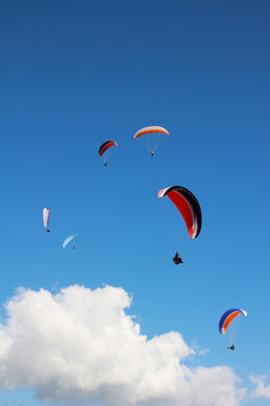 group of paragliders, floating in cloudy sky