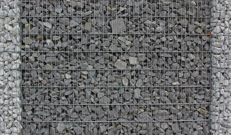 gabion mesh: gabion fence filled with granite stones, easy care garden fence Stock Photo
