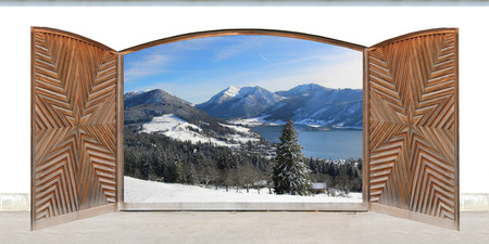 carved open double door with wintry lake view and mountains, german winter wonderland photo