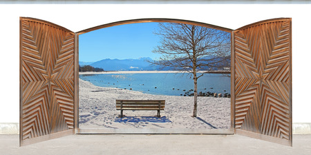 carved wooden double door with wintry lake view and mountains photo