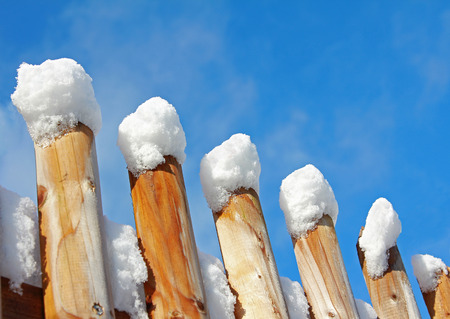 wooden fence with snow caps, blue sky photo
