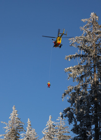 rescue helicopter: Alpine rescue helicopter in the mountains, paramedic saving a badly insured person