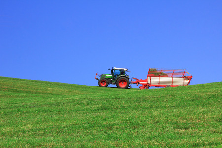 tractor with hayrack, harvesting animal forage