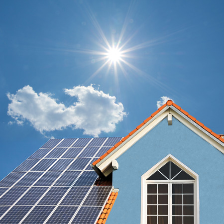 solar panel roof: modern new built house, rooftop with solar cells, blue front and bright sunshine