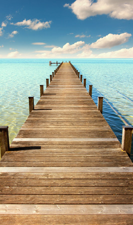 boardwalk to the horizon, turquoise water and blue sky with clouds
