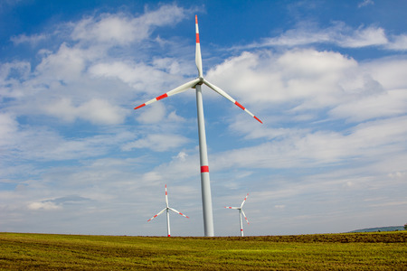 wind force wheel: group of windmills in the landscape, agains blue sky with clouds