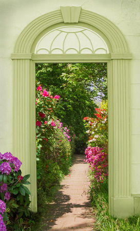 arched: view through arched door, colorful blooming rhododendrons