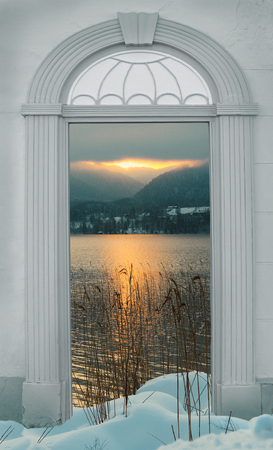 view through door: view through arched door, sunset at wintry lake in the alps