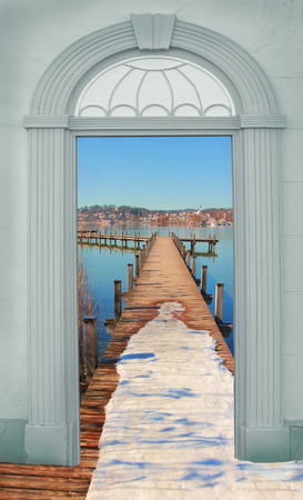 view through door: view through arched door,wintry boardwalk at the lake Stock Photo