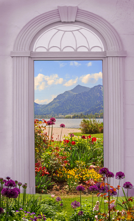view of a wooden doorway: view through arched door idyllic lakeshore with flowerbed Stock Photo