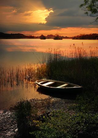zonsondergang meer met roeiboot en toneel