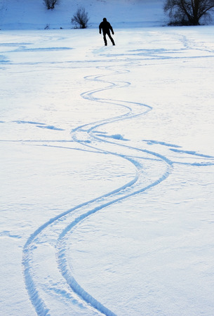 sinuous: ice skating man on a snow covered lake, sinuous line Stock Photo