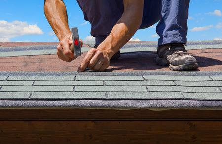 庭師は、タール紙帯状疱疹で夏の庭の家の屋根を更新します。
