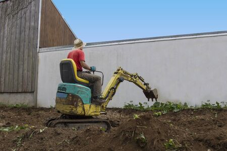 smoothing: man driving a mini digger - smoothing the terrain