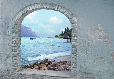 view through door: view through rustic vintage door to mountain lake and mediterranean landscape Stock Photo
