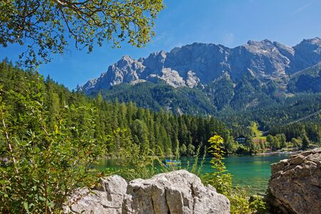 zugspitze mountain: picturesque lake eibsee with pedalo and zugspitze mountain, tourist destination bavaria. Stock Photo