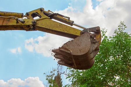 mini: shovel of a mini digger, transporting soil, blue sky and tree crown Stock Photo