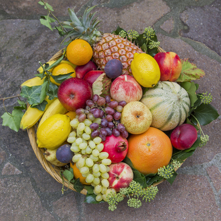 fruits in a basket: several fruits in a rattan basket with ivy leaves - thanksgiving decoration