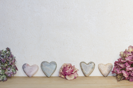 soapstone: marbled background with soap stone hearts and dried hydrangea and rose flowers