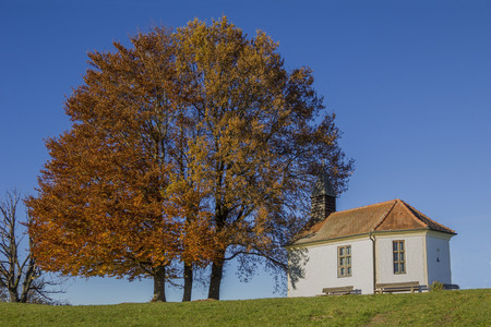 broad leaf: little chapel at the hill, beside autumnal trees, blue sky background Stock Photo