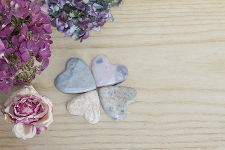 soapstone: four leaf clover figured with soap stone hearts and dried blossoms on wooden background