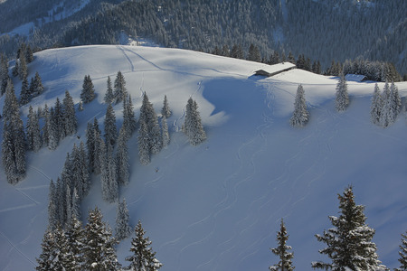 powder snow: alpine cabin at the hillside, fresh skiing tracks in the powder snow