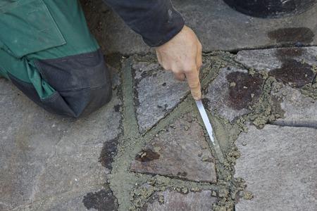 flagstone: man grouting porphyry flagstone patio with mortar Stock Photo