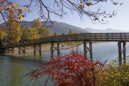 effluent: wooden bridge over mangfall river, effluent stream of lake tegernsee, in autumn landscape Stock Photo
