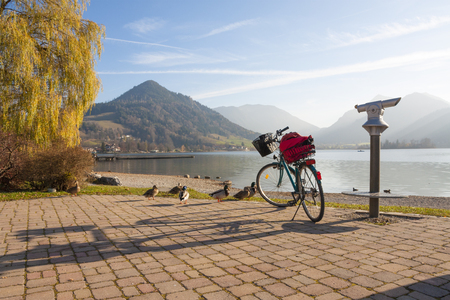 sightseeing at promenade lake schliersee in autumn, trekking bike and spy glass