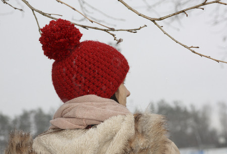 crocheted: young woman with self crocheted red woollen hat, outdoor in winter